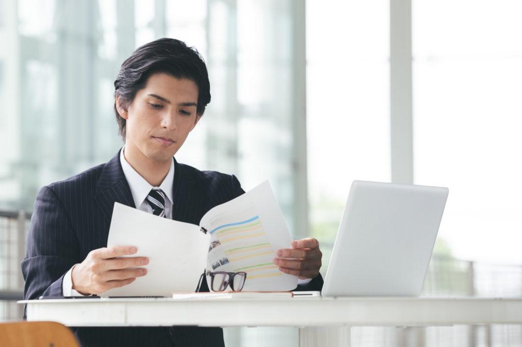 退職制度について就業規則を調べる男性